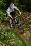 Mountainbiker i en kurva Arkivfoto