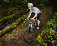 Mountainbiker i ett sluttande Arkivbilder