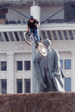 Mountainbiker makes a stunt in front of Lenin monument Stock Photo