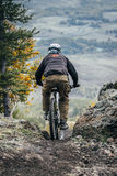 Mountainbiker preparing to descend the steep slope of the mountain Stock Photography