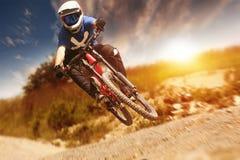 Mountainbiker-Sonnenuntergang-Spur abwärts Lizenzfreies Stockfoto