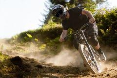 Mountainbiker-Staub-Fahrrad abwärts Stockbild
