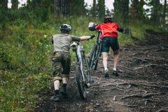 Mountainbiker två i skogen Arkivbild