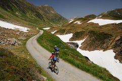 Mountainbikers骑马在阿尔卑斯 库存照片