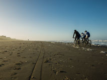 Mountainbikers on the beach. Early in the morning Royalty Free Stock Photos