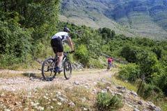 Mountainbikestörtlopp på en väg för gammalt land arkivfoto