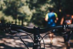 Mountainbikestyrestammen i parkerar med suddiga löpare Punkt av sikten royaltyfri foto