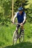 Mountainbiking sênior Imagem de Stock