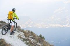 Mountainbile rest. Mountainbiker looks on the garda lake Royalty Free Stock Photos