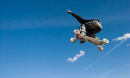 Mountainboard series. A mountainboarder in mid air with a deep blue sky in the background Royalty Free Stock Image