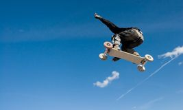 Mountainboard series. A mountainboarder in mid air with a deep blue sky in the background Stock Image