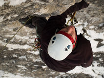 Mountaineer. Male climber ascending vertical cliff face. Winter Stock Photography