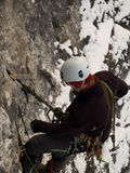 Mountaineer. Male climber ascending vertical cliff face. Winter Royalty Free Stock Photography