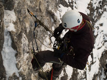 Mountaineer. Male climber ascending vertical cliff face. Winter Stock Photos
