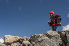 Woman mountaineer alone on rocks Stock Images