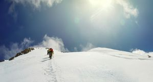 Mountaineer arrive to the summit of a snowy peak Stock Photos