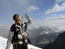Mountaineer after ascension. A portrait of young mountaineer taking a break at the summit of a high mountain. Ascension is over and now he's got time to enjoy stock photography
