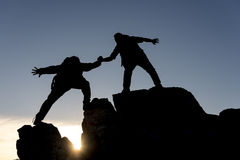 Mountaineer association. Mountaineering assistance and victory on peak Royalty Free Stock Photo