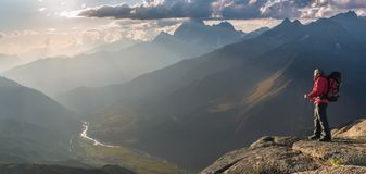 Mountaineer with backpack on rock stock photography