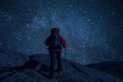 Mountaineer view of night sky with stars. Mountaineer with backpack on rock enjoying view of night sky with stars, hiking lifestyle, man on top royalty free stock photography