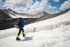A mountaineer with a backpack walks in crampons walking along a dusty glacier with sidewalks in the hands between cracks. A mountaineer with a backpack walks in royalty free stock images