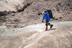 A mountaineer with a backpack walks in crampons walking along a dusty glacier with sidewalks in the hands between cracks. In the mountain royalty free stock photography