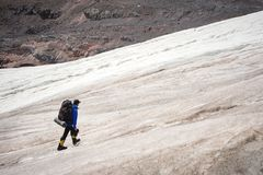 A mountaineer with a backpack walks in crampons walking along a dusty glacier with sidewalks in the hands between cracks. In the mountain stock photos