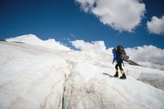 A mountaineer with a backpack walks in crampons walking along a dusty glacier with sidewalks in the hands between cracks. In the mountain royalty free stock image
