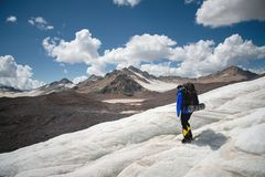 A mountaineer with a backpack walks in crampons walking along a dusty glacier with sidewalks in the hands between cracks. In the mountain stock photography