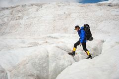 A mountaineer with a backpack walks in crampons walking along a dusty glacier with sidewalks in the hands between cracks. A mountaineer with a backpack walks in stock images