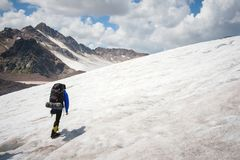 A mountaineer with a backpack walks in crampons walking along a dusty glacier with sidewalks in the hands between cracks. In the mountain stock image