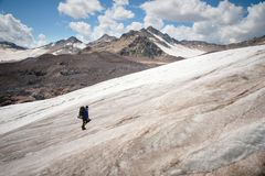 A mountaineer with a backpack walks in crampons walking along a dusty glacier with sidewalks in the hands between cracks. In the mountain royalty free stock images