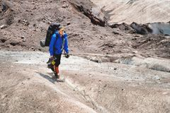 A mountaineer with a backpack walks in crampons walking along a dusty glacier with sidewalks in the hands between cracks. In the mountain stock images