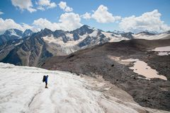 A mountaineer with a backpack walks in crampons walking along a dusty glacier with sidewalks in the hands between cracks. In the mountain royalty free stock photos