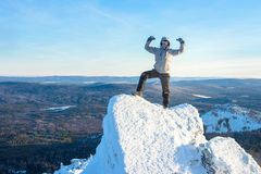 The mountaineer climbed the mountain top covered with ice and snow, man hiker standing at the peak of rock and. Celebrates the success. Winter season royalty free stock image