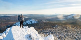 The mountaineer climbed the mountain top, man hiker standing at the peak of rock covered with ice and snow, view from. Back. Winter season stock photography