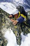 Mountaineer climbing snowy rock face stock photography