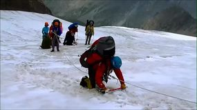Mountaineer crawling on the snow bridge over the crevasses stock video