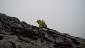 Mountaineer going up the mountain in foggy weather stock video