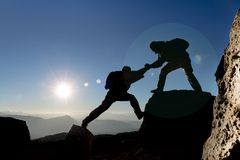Mountaineer helping another one. A mountaineer helping another one up a cliff royalty free stock photos
