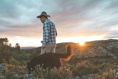 Mountaineer with his dog in the mountains. Guy and dog stock photography