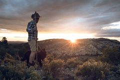 Mountaineer with his dog in the mountains stock photography