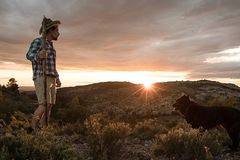 Mountaineer with his dog in the mountains. Guy and dog stock images