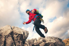 Mountaineer jumps over rocks in mountin. Cloudy weather royalty free stock photography