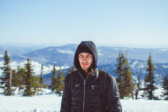 The guy is standing in the mountains in winter stock photo