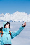 The mountaineer pointing at peak, standing against a winter mountain landscape. Stock Images