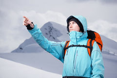 The mountaineer pointing at peak, standing against a winter mountain landscape. Royalty Free Stock Photography