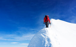 Mountaineer reach the summit of a snowy peak. Concepts: determin. Ation, courage, effort, self-realization. Clear sky, sunny day, winter season. Large copy-space Royalty Free Stock Photos