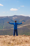 Mountaineer reaches the top of a mountain in sunny. Hiking man on top of the mountain happy and celebrating success. Male hiker on top of the world cheering in Stock Photography