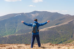 Mountaineer reaches the top of a mountain in sunny. Hiking man on top of the mountain happy and celebrating success. Male hiker on top of the world cheering in Royalty Free Stock Image